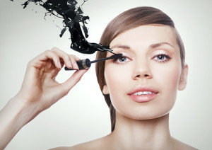 woman with mascara brush and black splash